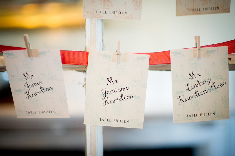 Escort cards were printed with the same toile used in the envelope liner in faint contrasting colors and strung from ribbon.