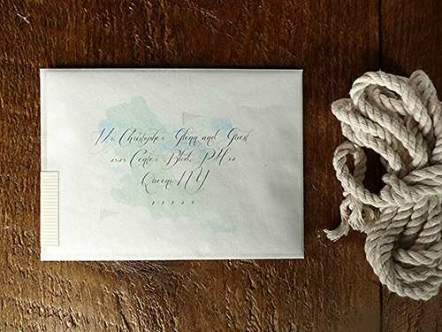 A simple folder printed with the couples names is nestled inside a transparent vellum envelope. A map of Newport printed on the back of the folder can be seen through the envelope behind the address.