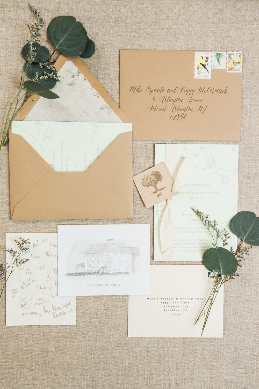 The main card, letterpress printed in pale gray on a duplexed pale green card, was inspired by spring with whimsical buds and leaves floating around a simple but vintage type treatment. We chose a handmade paper envelope liner with real leaf inclusions to echo the printed flowers on the invitation