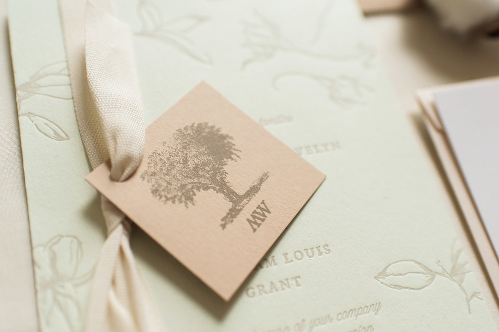 "Sheffield has a ""Big Elm"" tree in the center of town so we created a logo and monogram tag, tied to the invitation with an understated cotton twill ribbon."