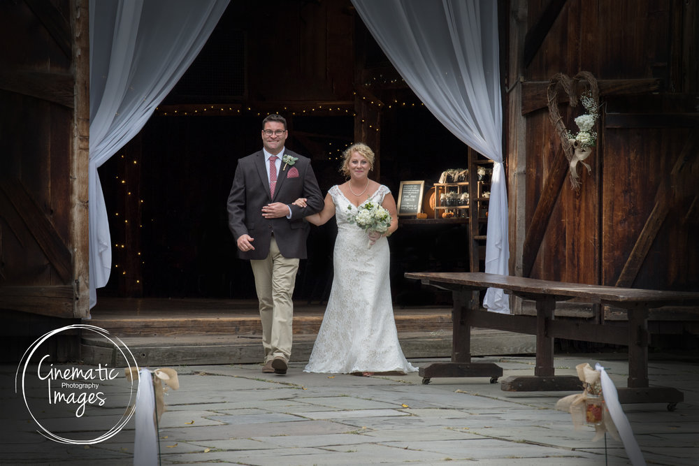 BRIDE WALKING UP AISLE AT RUSTIC BARN WEDDING