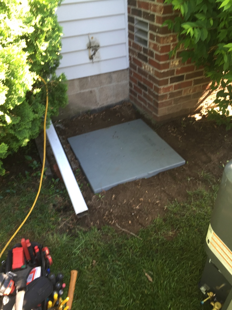 D'Angelo's Plumbing & Heating is preparing the ground and pad for an air conditioner installation in Rochester, NY