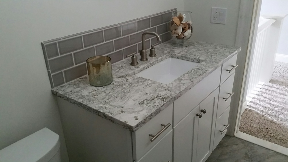 Diamond Vanity with quartz top.  Back splash is tiled to match the shower.