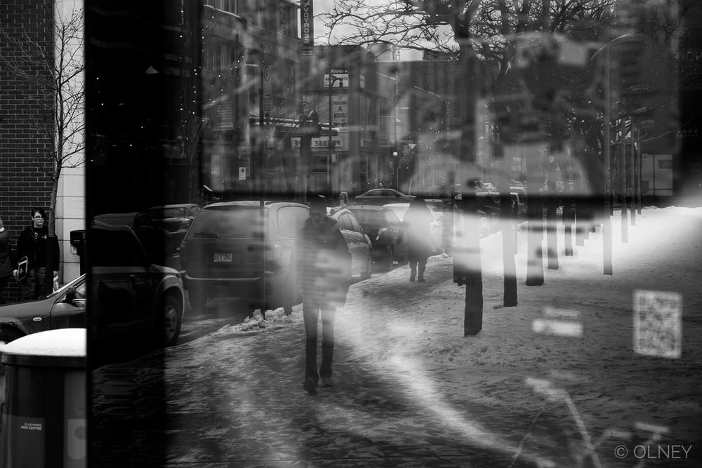 Reflet de passant sur un panneau de bus à Montréal photographie de rue olney photographe sherbrooke