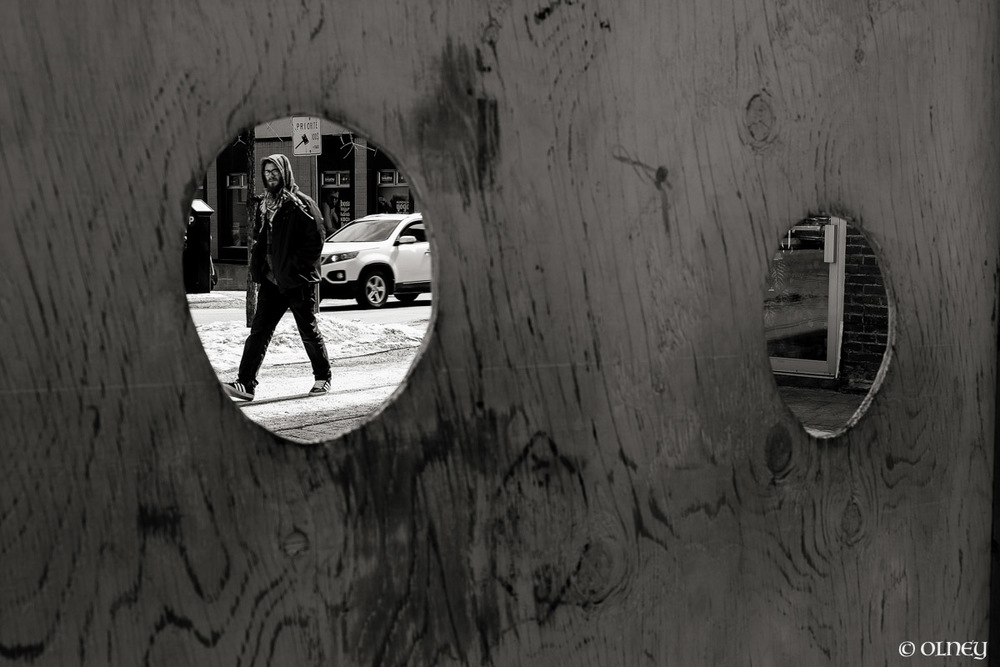 Men walking seen by a hole in a woodden wall photographie de rue olney photographe sherbrooke
