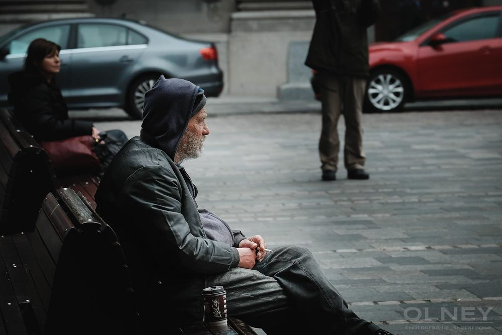 Homeless sitting in Place d'Armes in Montreal