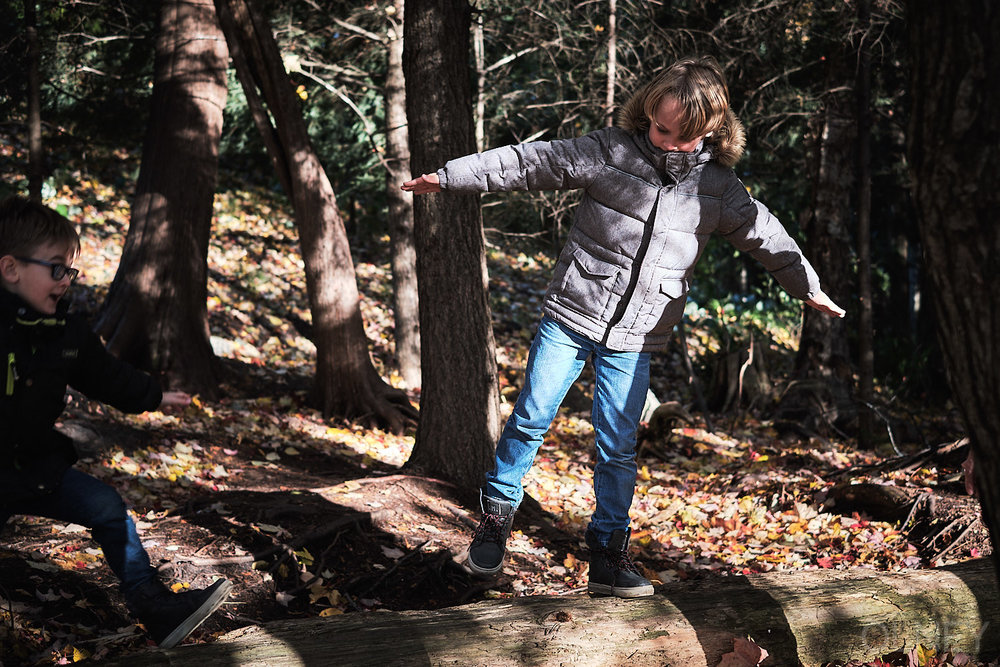 kid standing on a log
