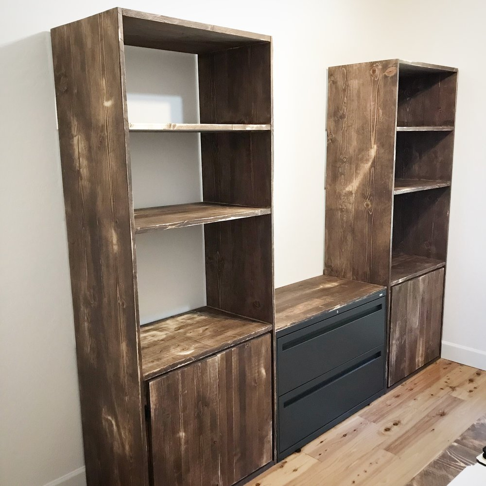 Custom wood shelving towers bridged with a double file cabinet.