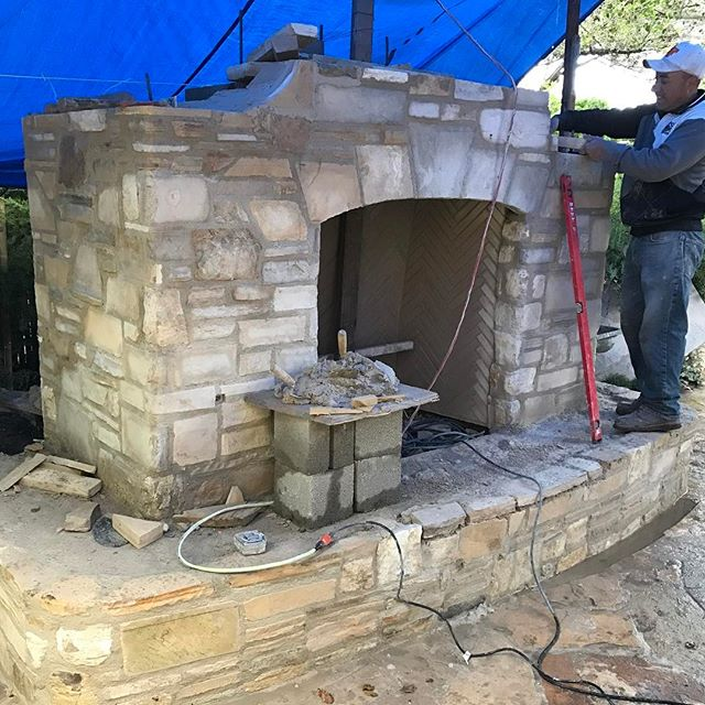 Working on a new outdoor, gas fireplace in the rain last week.