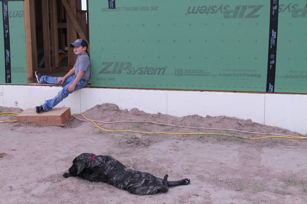 Cory Toye's son Joe lounges with his dog Tiny while his dad goes over details with the homeowners.