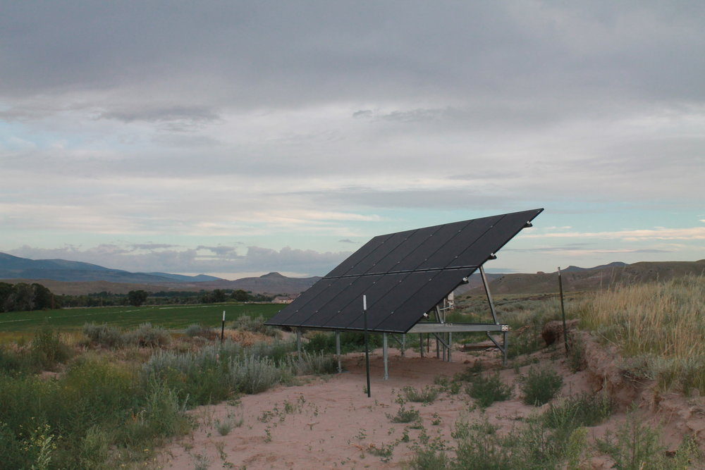 Solar panels sit next to the construction site at the Crowheart project.