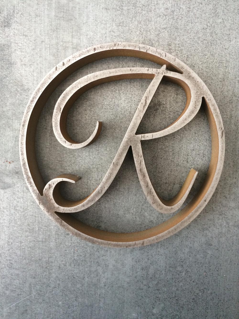 """R"" medallion"