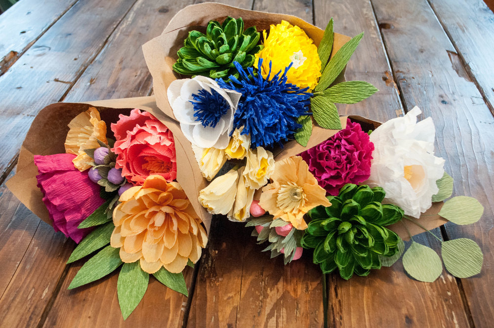 Build these 6-stem bouquets! Left bouquet recipe: magenta peony, gold poppy, salmon peony, gold dahlia, purple berries, grass green leaves. Middle bouquet recipe: anemone, green succulent, yellow Japanese ranunculus, blue thistle, yellow sweet pea, grass green leaves. Right bouquet recipe: cream peony, green succulent, magenta Japanese ranunculus, gold poppy, salmon berries, silver dollar eucalyptus.