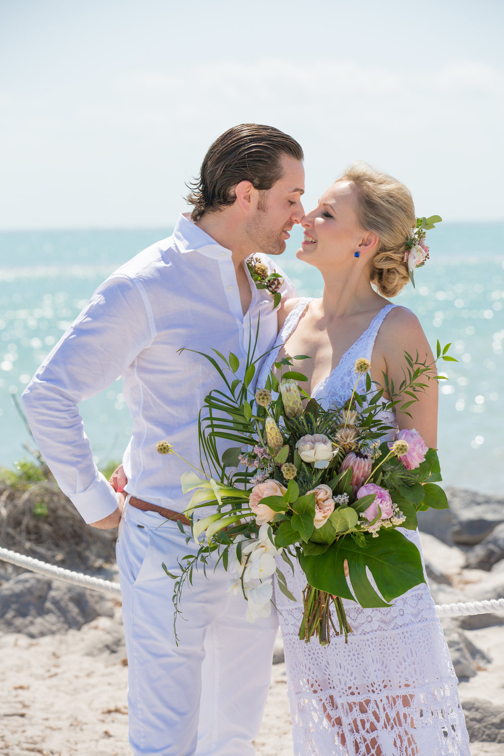 Bride and groom at Key Biscayne wedding with tropical bouquet