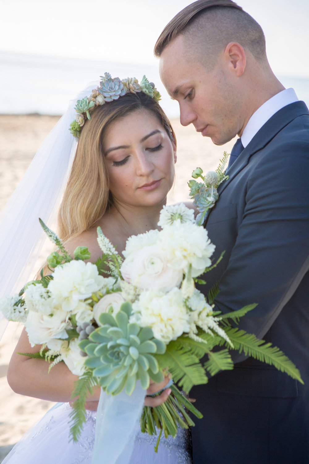 Bride with natural wedding bouquet and flower crown at beach wedding with groom