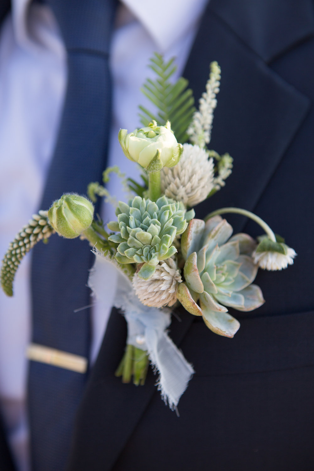 Close-up of groom's boutonniere at beach wedding with succulents