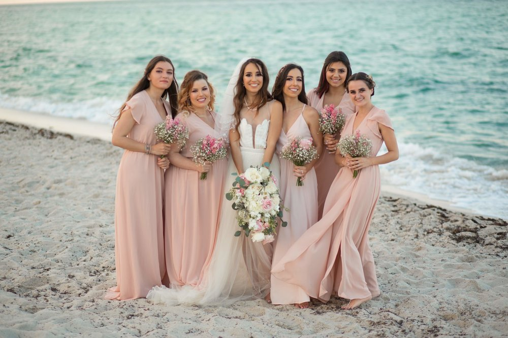 Mermaid wedding party with bride bouquet and bridesmaids bouquets with white and blush flowers at Miami Beach wedding