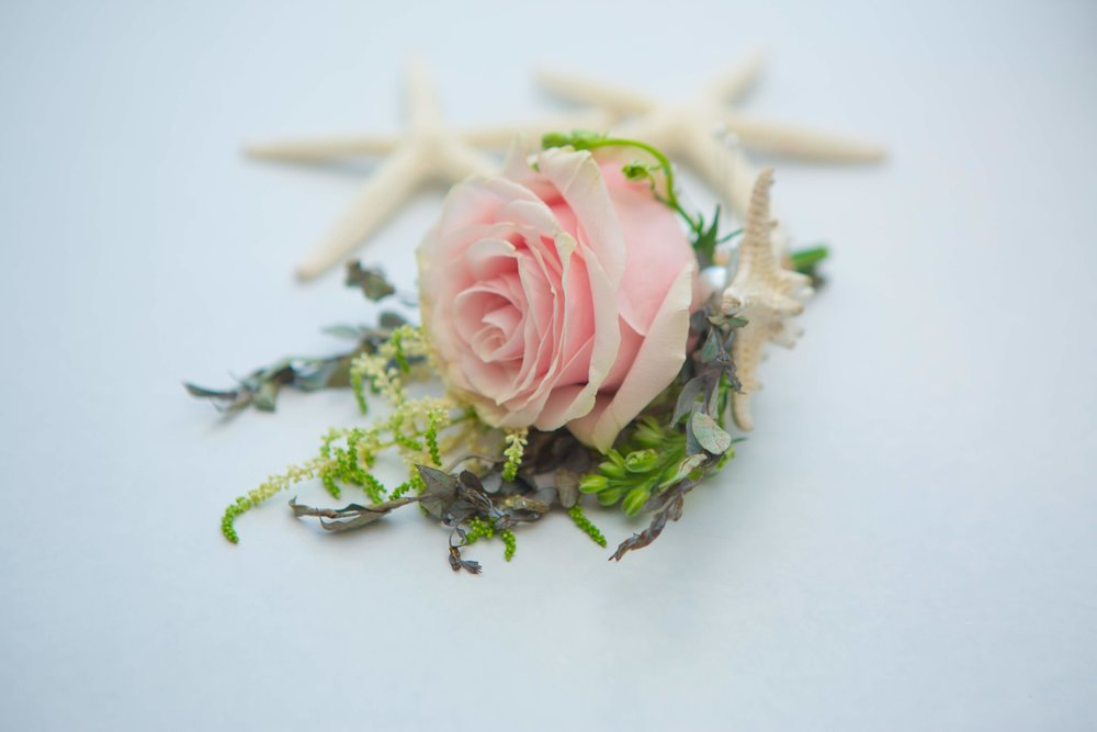Grooms boutonnière for mermaid wedding in Miami Beach with pink rose and starfish