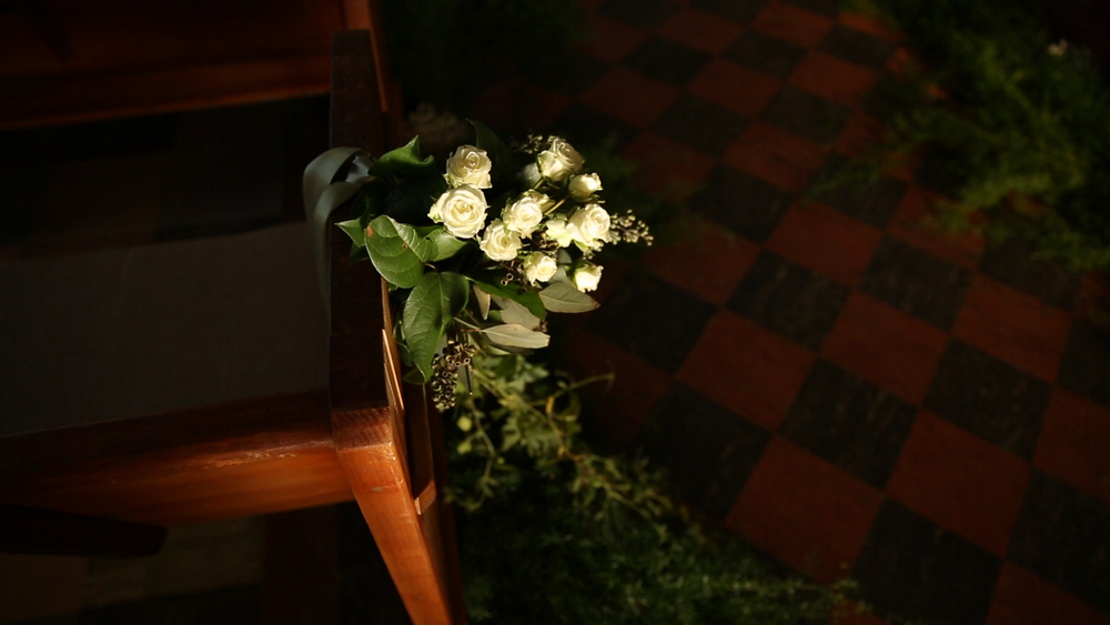 Beautiful greenery and white roses accented the aisle at the Marigny Opera House.