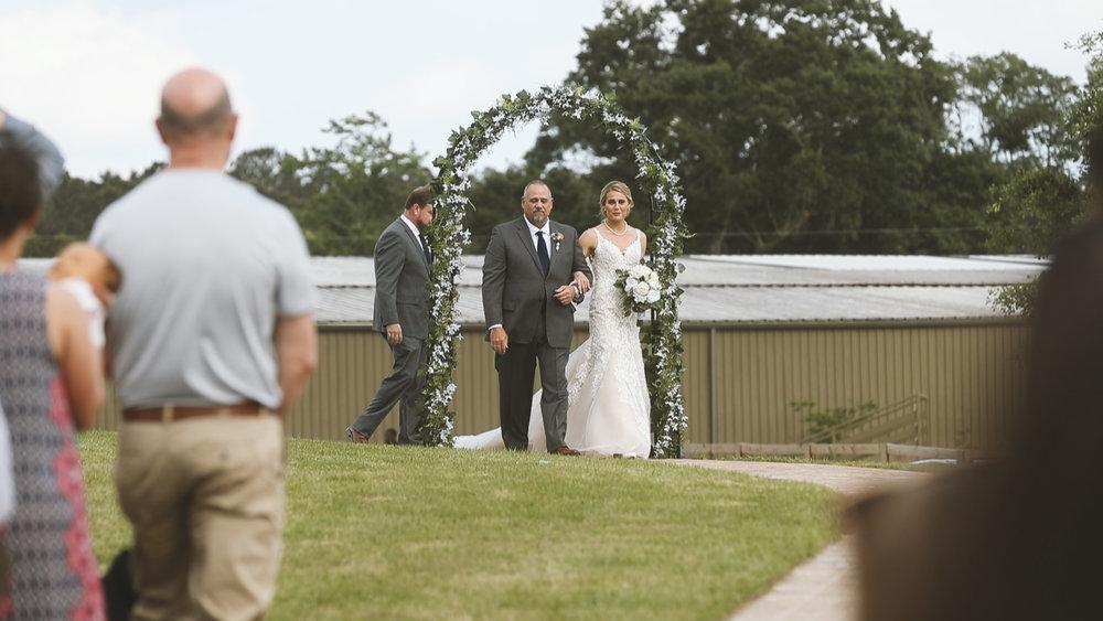 Amanda and Hayden_The White Magnolia Farm Weddings_New Orleans videographer_Bride walking down outdoor wedding aisle