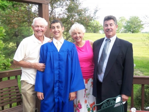Shane graduating from Moller High School with his grandpa (left) and parents.