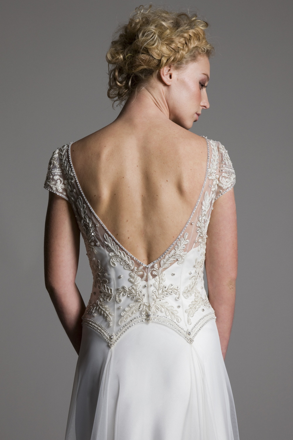 Detailed back view of the Marianne embellished beaded detailed cap sleeved bodice with tulle skirt on top of a V neck ivory satin slip bridal wedding dress by Halfpenny London