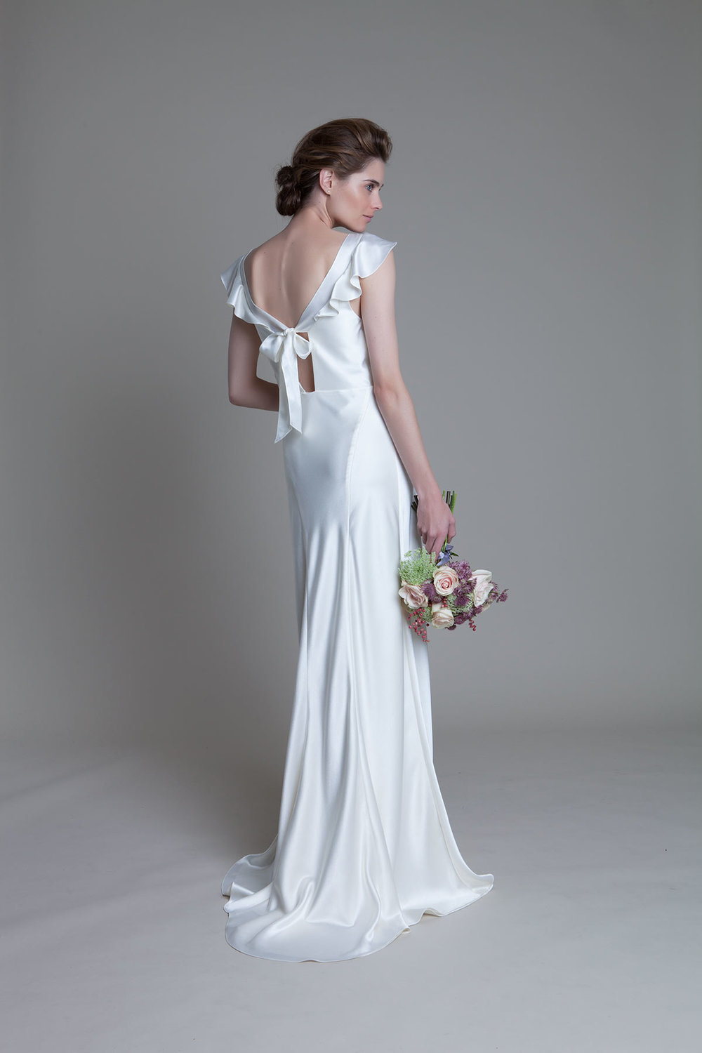 Back view of the Sarah soft cowl neck and empire line bias cut satin bridal wedding dress by Halfpenny London