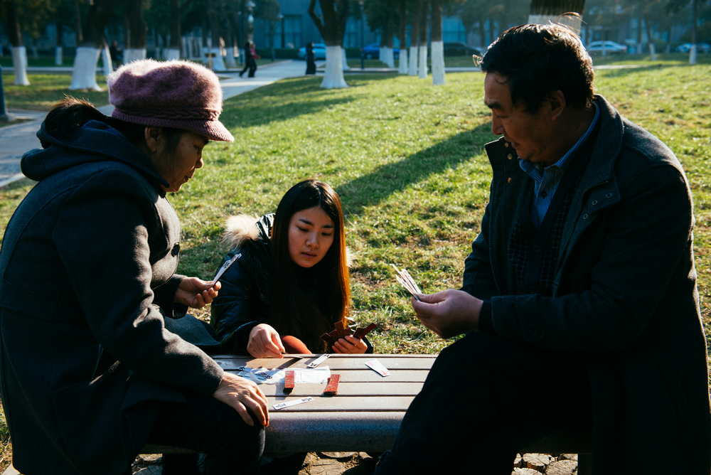 "In the grass area right next to the tomb of Matteo Ricci, in an area that was probably the grave yard of the first Christian cemetery in China, three people play Maquepai, or ""Sparrow Cards""."