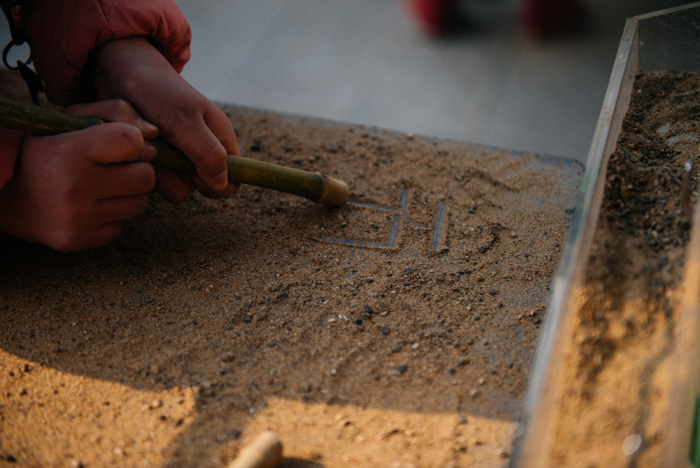 Behind the temple there is a museum with activities for children. Here a child inscribes in sand the word stone (石 ).