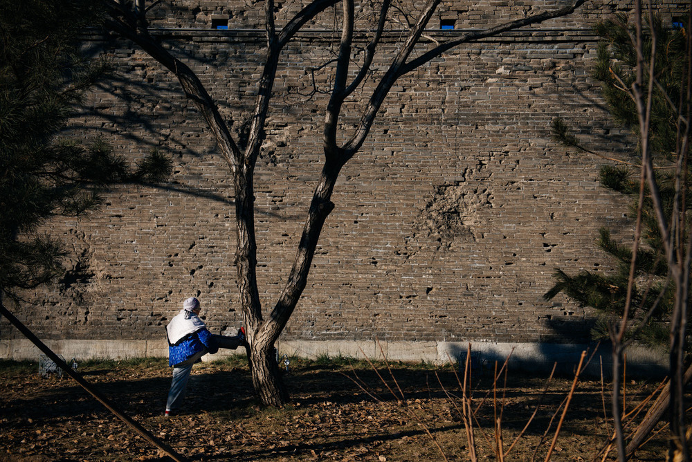 Old lady stretches for her morning exercise outside the Wanping fortress. Battle marks are clearly seen on the wall.