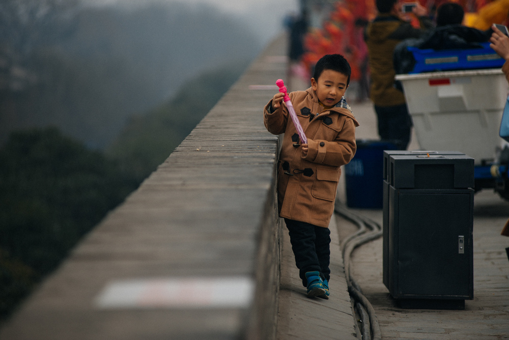 During spring festival, when I went, the top of the wall had dozens of intricate lanterns, divided into groups representing several countries around the world. They would light up at night, forming a beautiful constellation of lights. This kid was blowing soap bubbles and running around through the lanterns.