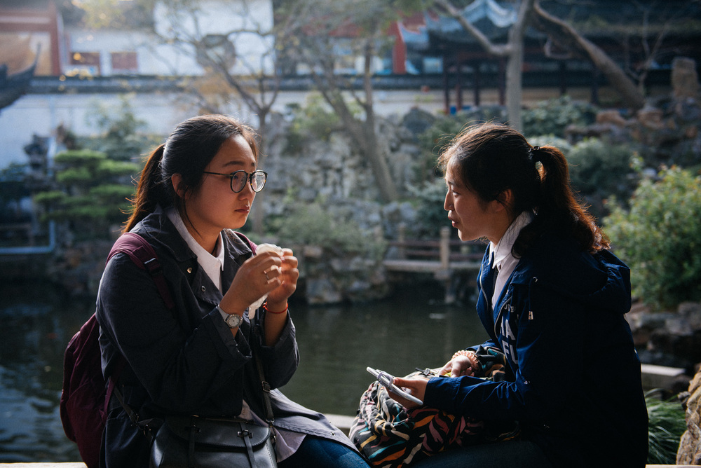 Girl cries sitting on a bridge while a friend talks to her as the sound of water from the artificial lake below hides from the dozens of tourists walking by whatever they were saying.