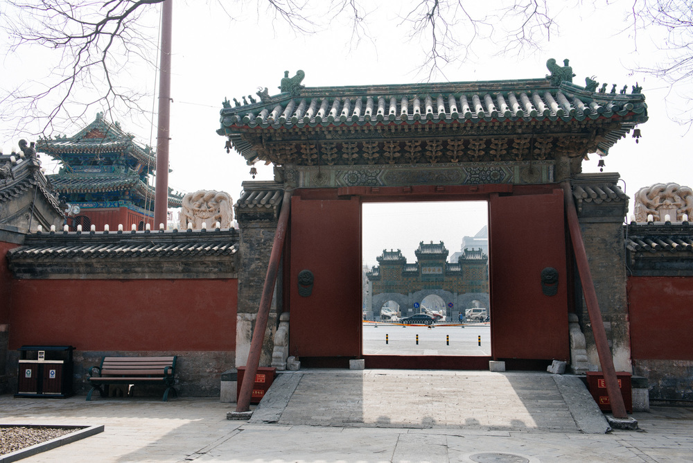 On the other side of a busy street in front of the temple is a large gate.