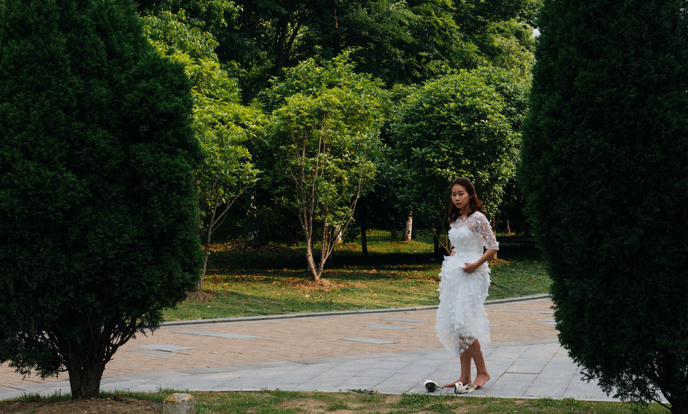 As I mentioned before, these photographic session can last hours or even days. It can be extremely tiring to walk in heels all day while someone keeps telling you to stand straight and smile. This bride takes a rest in a park while the photographer prepares for the shoot.