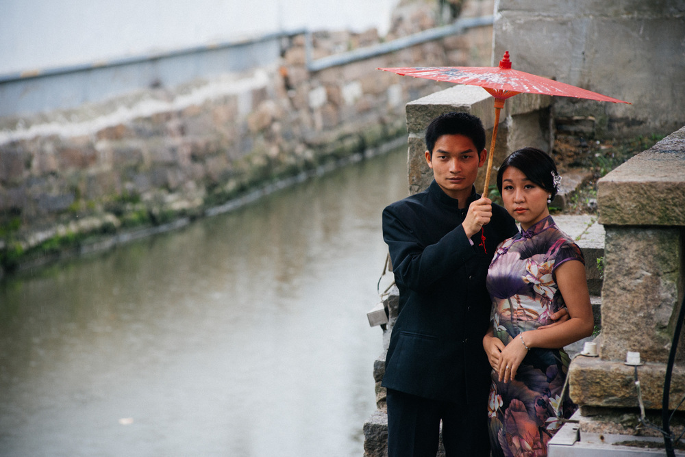 Couple poses in traditional Chinese attire in front of one of the canals in the old town on the ancient Pingjiang Road. The bride and groom are protecting themselves against the rain with the help of a traditional umbrella made with rice paper.
