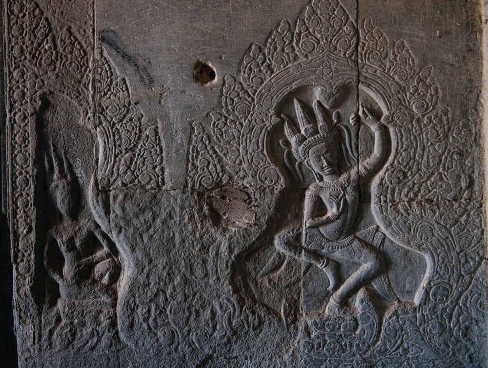 Engraving in the outer corridor of the Wat with what seems to be a bullet hole, from the confrontations between the Vietnamese and the Khmer Rouge.