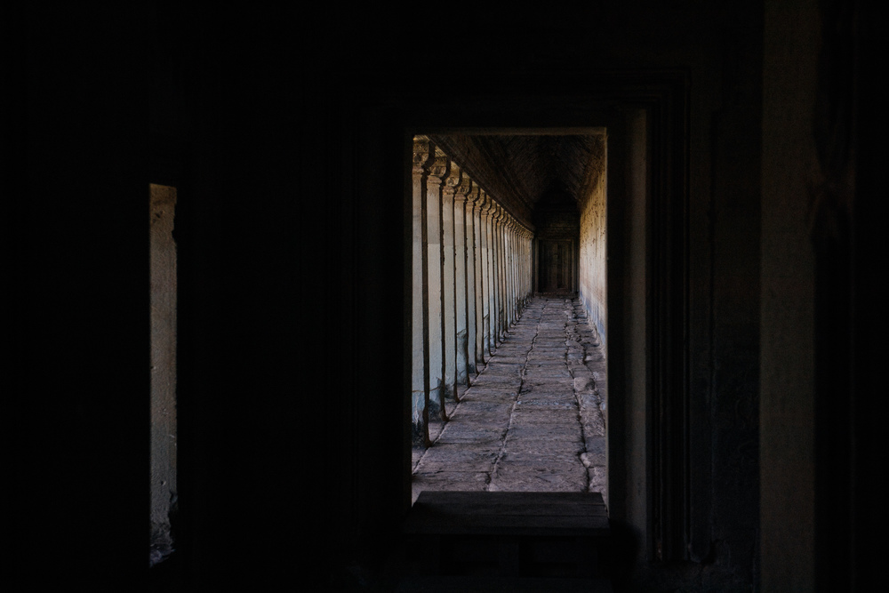 Angkor Wat has a huge corridor surrounding the temple like a frame. Along the walls are inscriptions of great battles of the Khmer empire. View from inside the Gallery of 1000 Buddhas into the Battle of Lanka corridor.