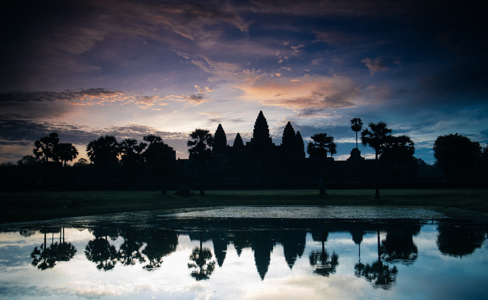 Sun rises behind Angkor Wat, which unusually faces west, on a hot and humid summer day during rainy season. I was very lucky to get a good sunset on that day, as it rained constantly.
