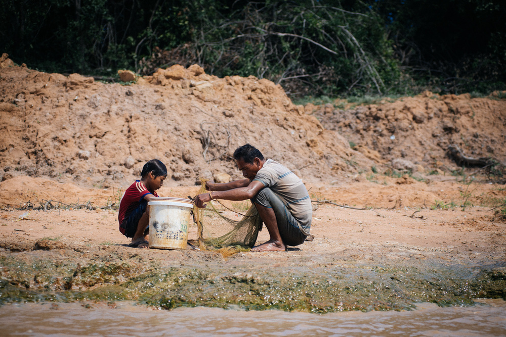 Along the margins of the Siem Reap river, a man and a boy, father and son perhaps, prepare their net for fishing.