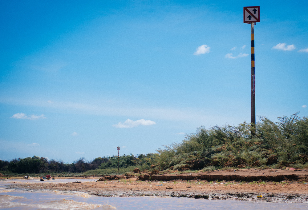 A marker built to show the water level and warn of floods now sits on a dry sand bank with vegetation. Regular water levels should be around the middle of the post, at least ten meters over what they were in June 2016 when I visited.