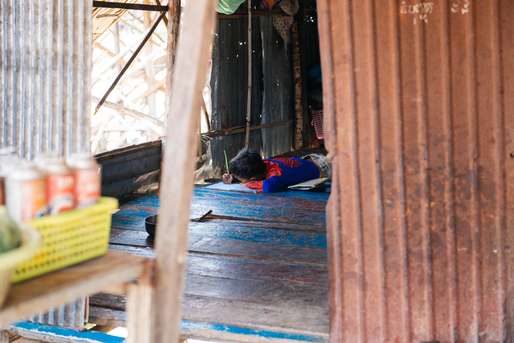 While the other kids played outside in the water, this boy stayed inside attentively doing his homework. In the nearby floating village and at the Angkor Wat parks, many children work selling souvenirs to tourists instead of going to school.