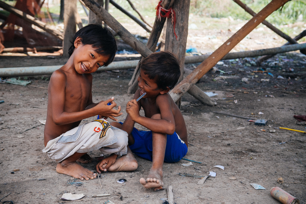 Boys in a village on the banks of the Siem Reap play with a broken pen and a plastic gun that shoots rubber bands.
