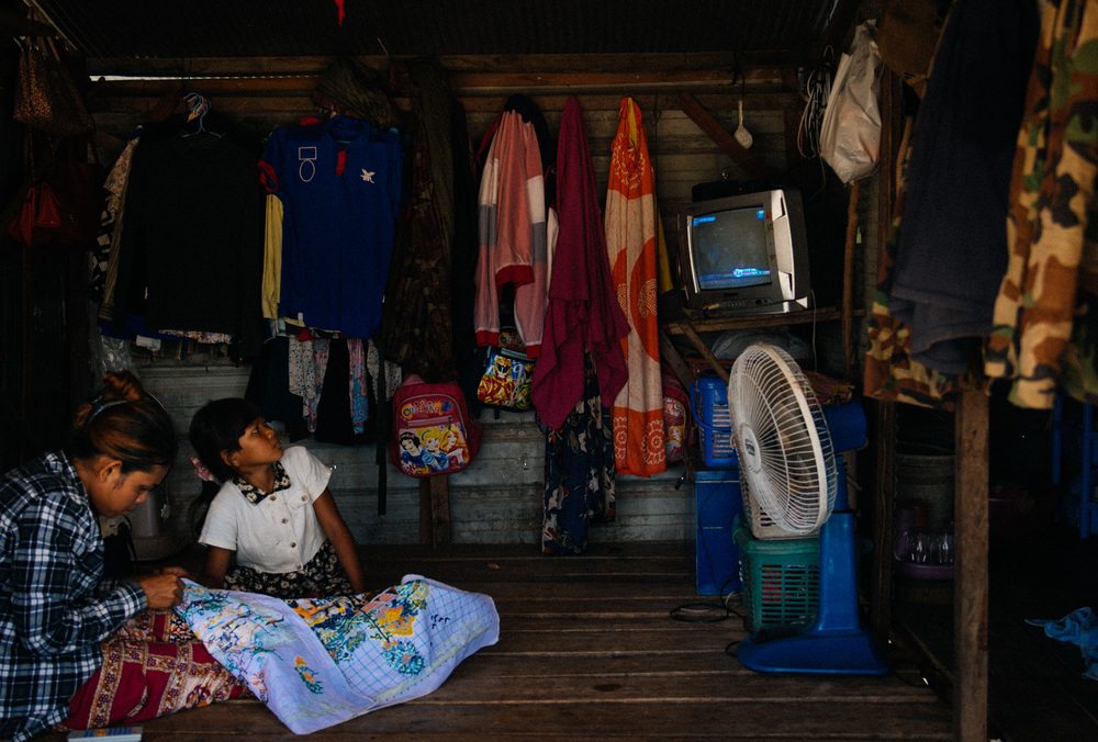 Girl watches television while another sews inside their house. Like this place, most shacks have only one room where several people sleep either on the ground or in hammocks.