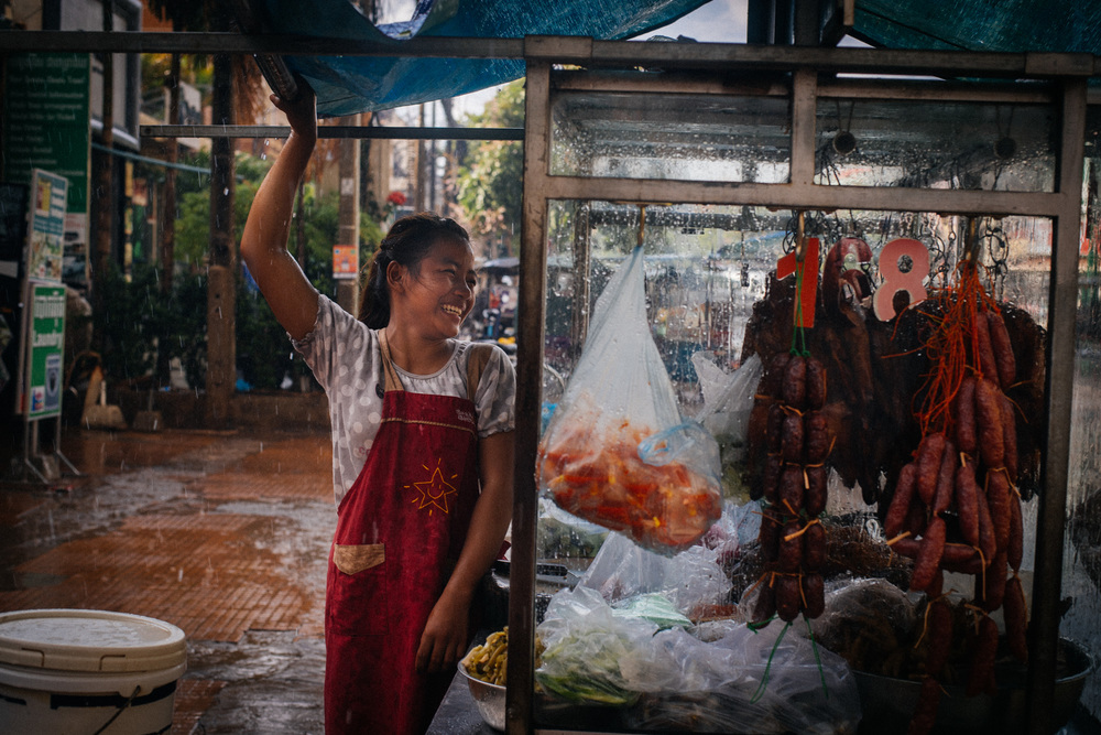 Street vendor talks to her colleague while both protect themselves and the food from the pouring rain in downtown Siem Reap.