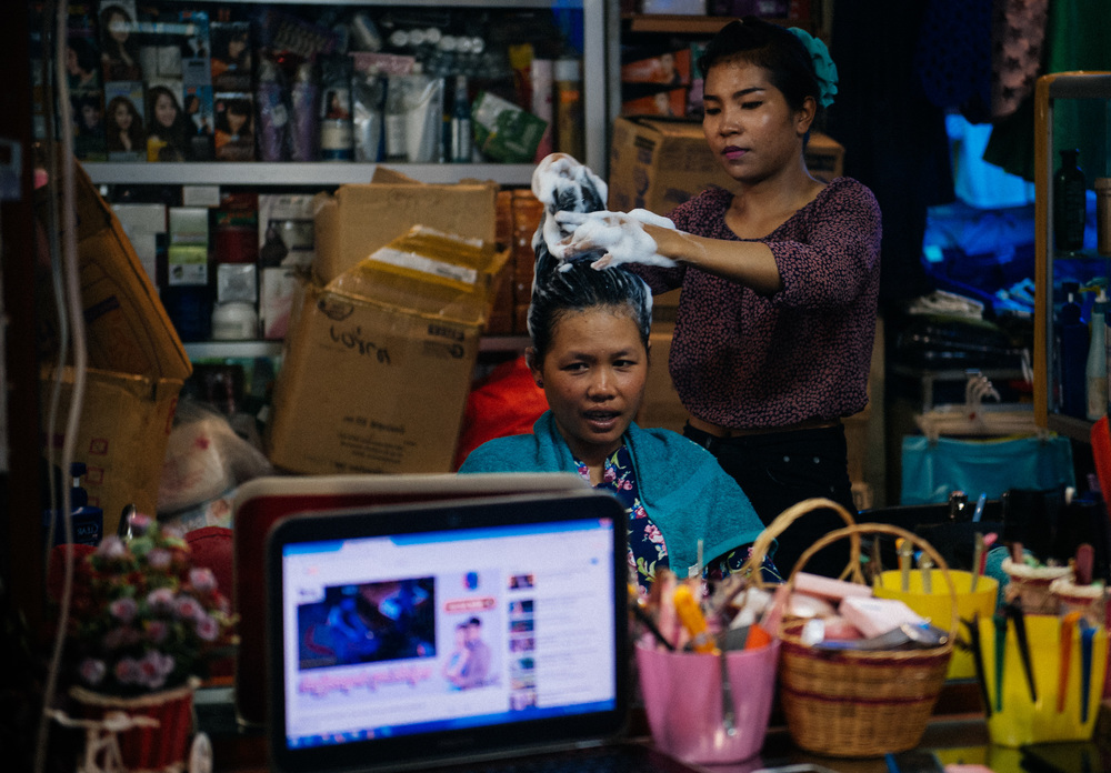 Woman gets her hair done in the market while they watch a soap opera online on the computer. Every single market I went to had a hairdresser.