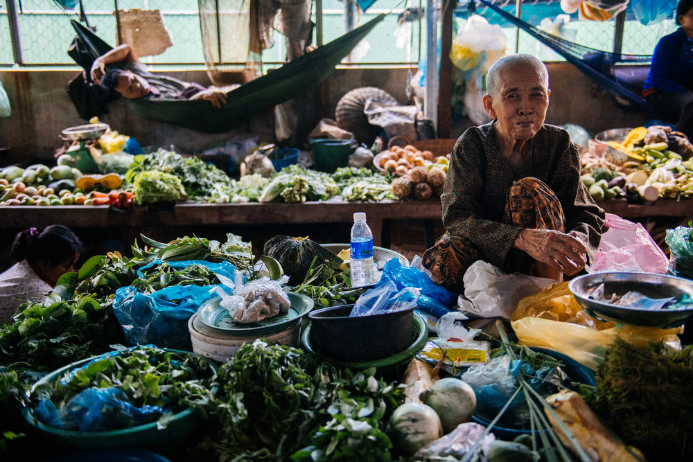 Vendor crouches on the table with the vegetables she is selling, waiting for customers.