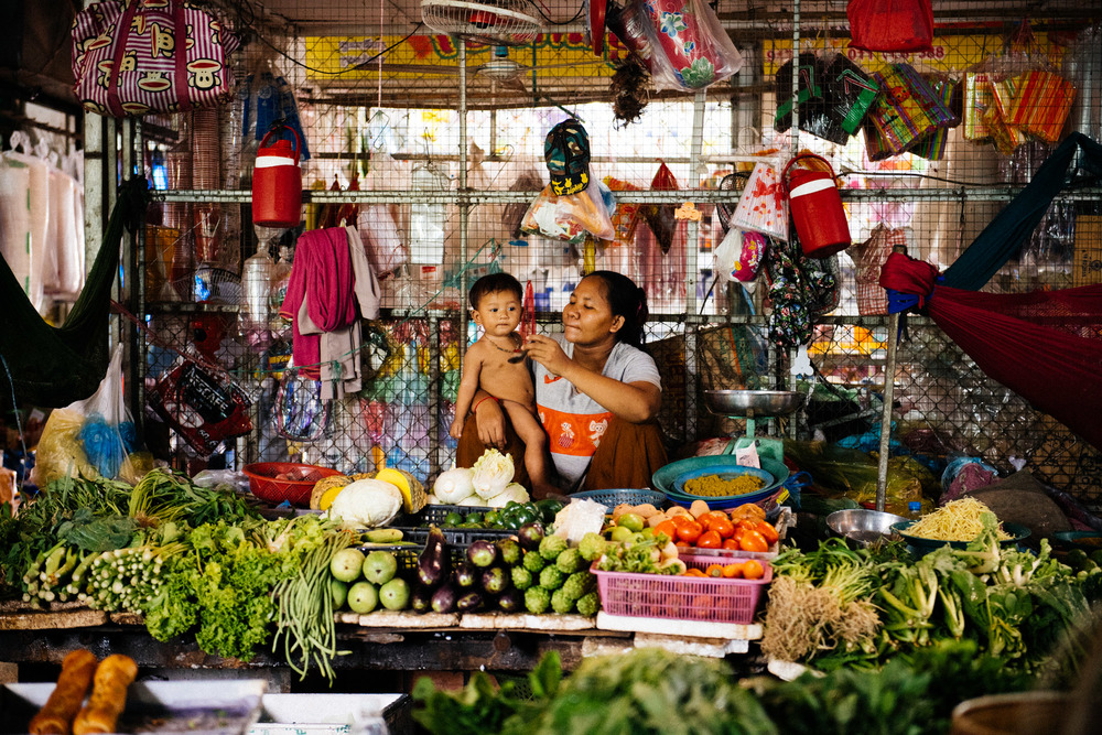 Vendor feeds her son under a fan in the humid and extremely hot market.