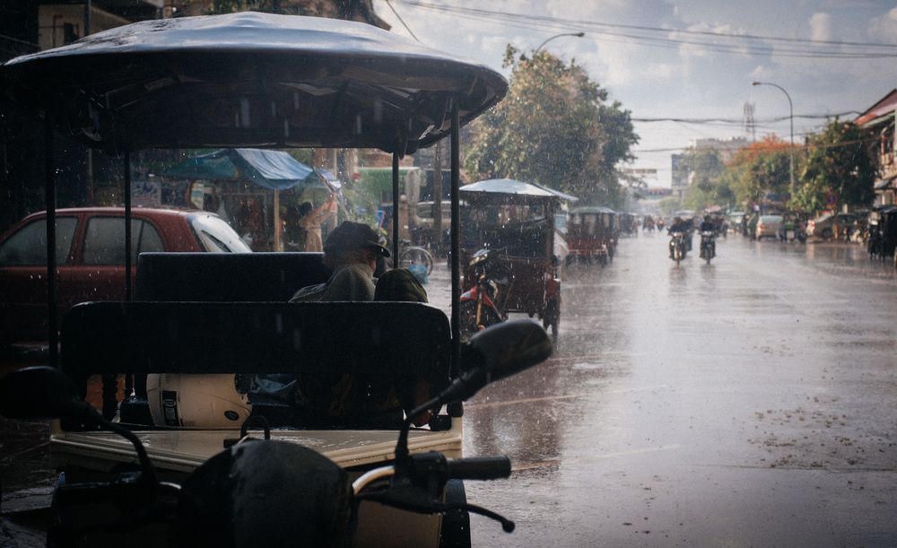 Tuk-tuk driver sleeps through the heavy rain and doesn't even bother to protect himself from the falling water.
