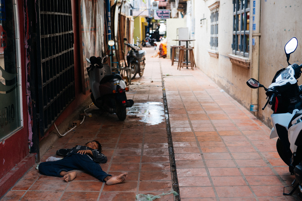 Boy sleeps on the ground next to a bookstore on the bar street in downtown Siem Reap.