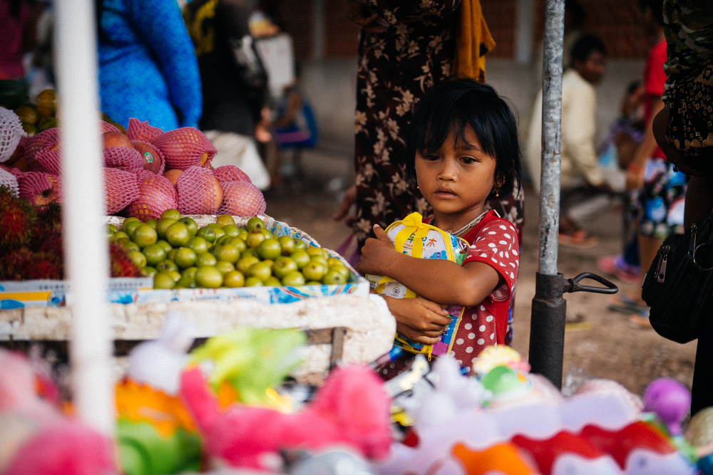 Little girl with something in her eye clings to her backpack as she browses fruit at a market across the street from the children's hospital.